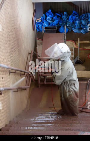 worker in protection suit sandblasting a wall - Stock Photo