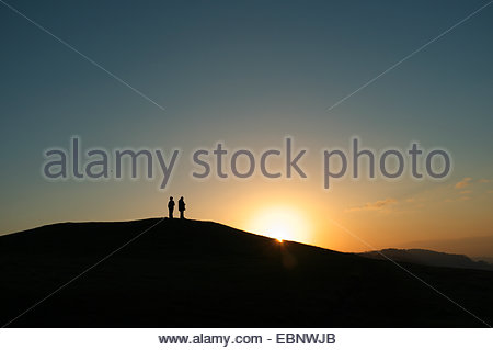 Stroud, Gloucestershire, UK. 3rd December 2014. UK Weather: Two people enjoy watching the sun going down from this - Stock Photo