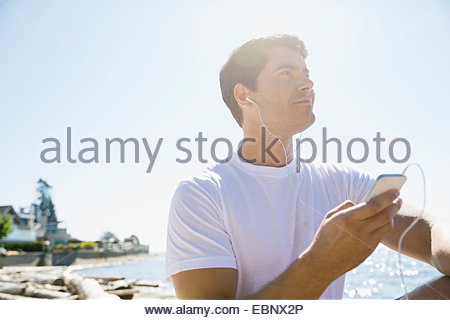 Runner listening to mp3 player on beach - Stock Photo