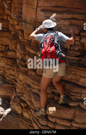 female wanderer climbing at a rock wall in the Naukluftberge Mountains, Namibia, Namib Naukluft National Park