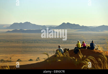group sitting on a dune in the desert and enjoying the view, Namibia, Namib Naukluft National Park, Sesriem Camp - Stock Photo