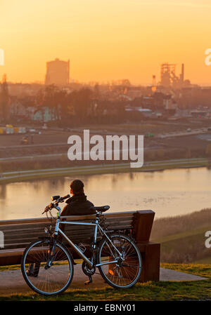 cyclist sitting on a bench, having a break and enjoying the sunset at Lake Phoenix, Germany, North Rhine-Westphalia, - Stock Photo