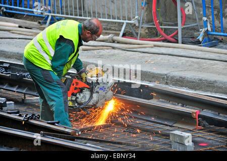 worker with abrasive cut-off machine working on tram lines, Czech Republic, Prague - Stock Photo