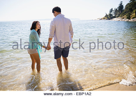 Couple holding hands and wading in ocean - Stock Photo