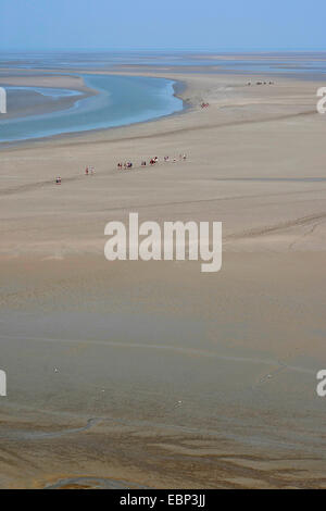 sandy tideland at low tide with tidal flat hikers, France, Brittany - Stock Photo