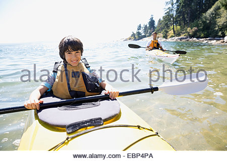 Portrait of father and son kayaking in ocean - Stock Photo