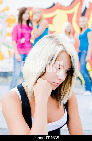 schoolgirl sitting in the schoolyard frustrated, schoolmates in the background slagging her off - Stock Photo