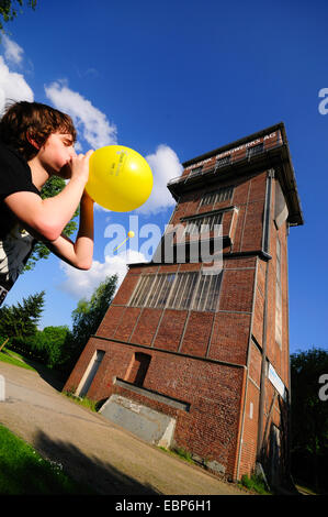boy blowing up a yellow balloon in front of headframe and big yellow balloon 'Schachtzeichen', Germany, North Rhine - Stock Photo