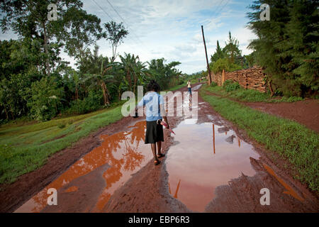 woman with umbrella and handbag is walking on a path that is soaked in water after a recent rainfall, Uganda, Jinja - Stock Photo