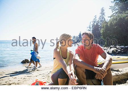 Couple talking on sunny beach - Stock Photo