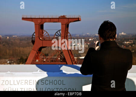 visitor taking photos from viewing platform to winding tower 12 of Zollverein Coal Mine Industrial Complex, Germany, - Stock Photo