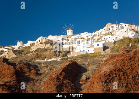 Ia, Santorini, South Aegean, Greece. View to the village from Ammoudi Bay, hilltop windmill prominent. - Stock Photo