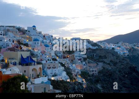Ia, Santorini, South Aegean, Greece. The clifftop village illuminated at dawn. - Stock Photo