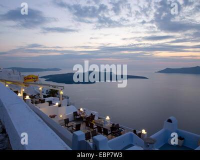 Firostefani, Santorini, South Aegean, Greece. View across the caldera at dusk, the volcanic island of Nea Kameni - Stock Photo