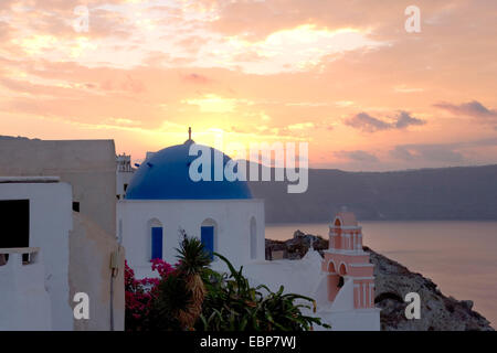 Ia, Santorini, South Aegean, Greece. Colourful dawn sky, typical blue-domed church in foreground. - Stock Photo