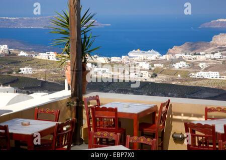 Pyrgos, Santorini, South Aegean, Greece. View over the caldera from terrace of a typical taverna, cruise ship in - Stock Photo