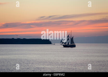 Ia, Santorini, South Aegean, Greece. Sailing ship passing in front of the island of Thirasia, dusk, pink clouds - Stock Photo