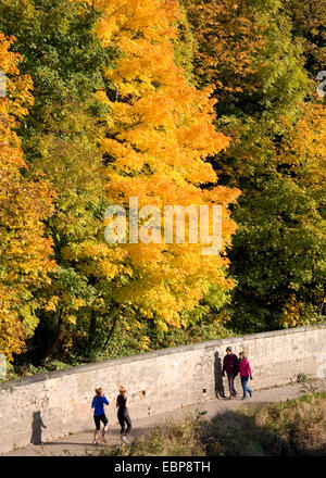 Durham, County Durham, England. Joggers and walkers on footpath beside the River Wear, autumn. - Stock Photo