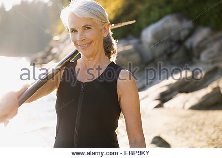 Portrait of senior woman in wetsuit on beach - Stock Photo