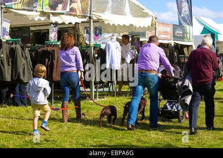 Family walking passed clothing stalls at Lowther Country Show. - Stock Photo
