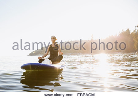 Senior woman meditating on paddle board in ocean - Stock Photo