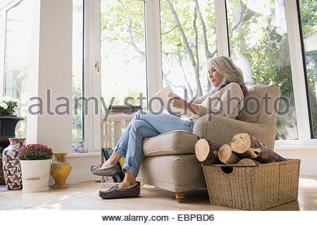 ... Senior Woman Reading In Armchair   Stock Photo