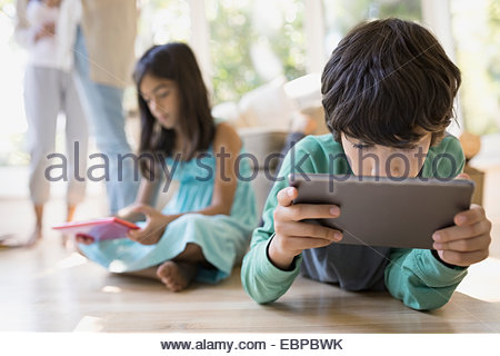 Boy using digital tablet on living room floor - Stock Photo