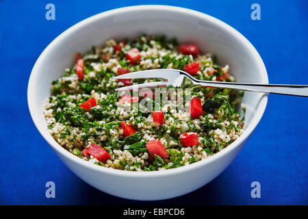 tabbouleh salad in a white bowl on a dark blue background with silver serving spoon and a fork - Stock Photo