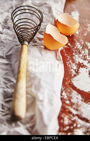 vintage whisk over a bowl with flour and an egg on top of parchment paper and wood table - Stock Photo