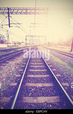 Vintage retro filtered picture of railway tracks and infrastructure. - Stock Photo