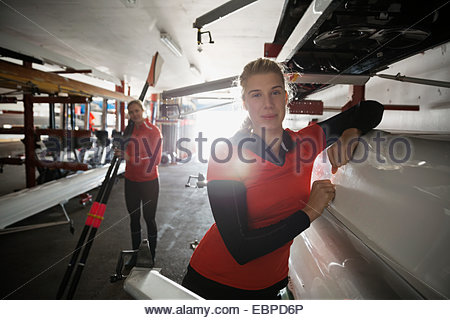 Confident rower leaning on scull in boathouse - Stock Photo