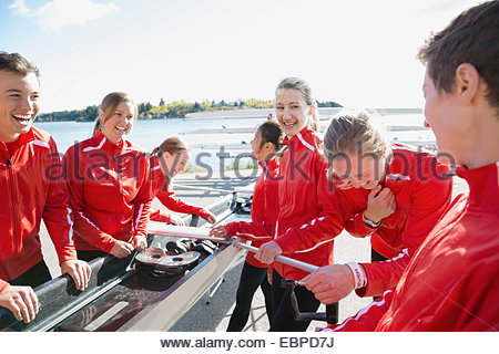 Rowing team laughing around scull - Stock Photo
