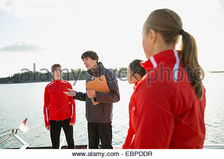 Coach talking to rowing team at waterfront - Stock Photo