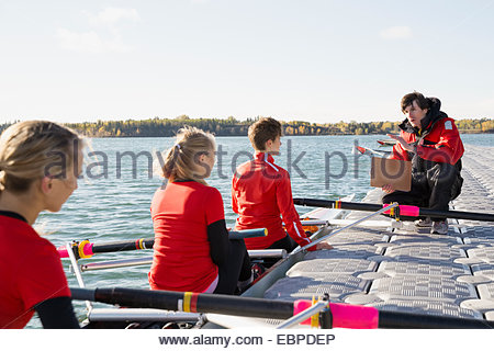 Coach talking to rowing team in scull - Stock Photo