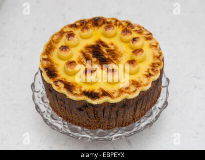 Traditional uncut home baked Easter simnel cake, topped with toasted marzipan balls, on a glass cake stand - Stock Photo