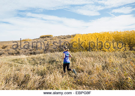 Woman running in sunny rural field - Stock Photo