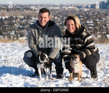 Couple with Boston Terrier and Bugg (cross between Boston Terrier and Pug) dogs in city park
