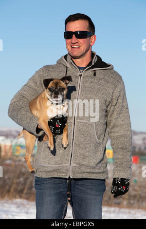 Man holding his Bugg dog (cross between Boston Terrier and Pug) in city park