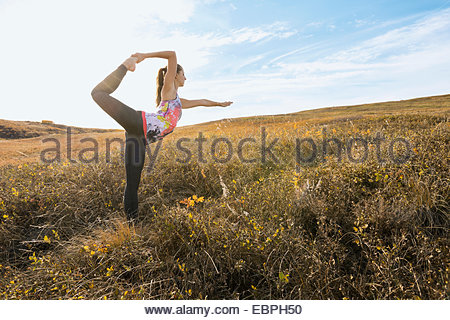 Woman practicing yoga in sunny rural field - Stock Photo