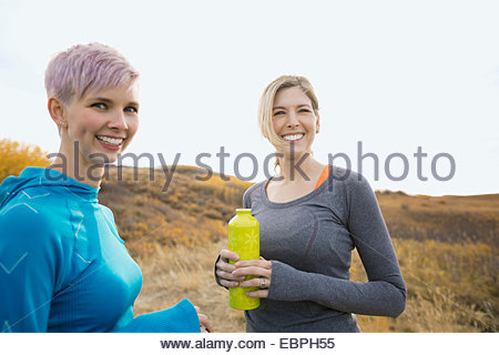 Women with water bottles talking in rural field - Stock Photo