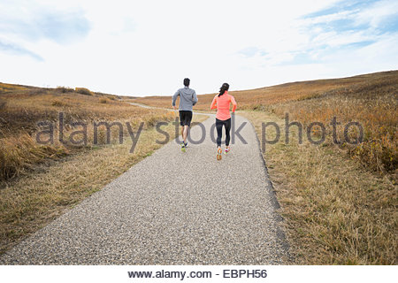 Couple running on rural path - Stock Photo