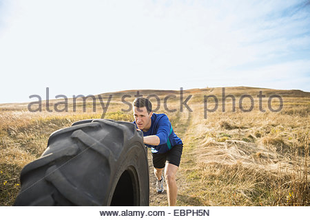 Man pushing crossfit tire in sunny rural field - Stock Photo