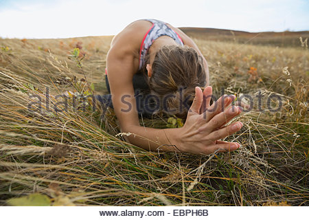 Serene woman practicing yoga in rural field - Stock Photo