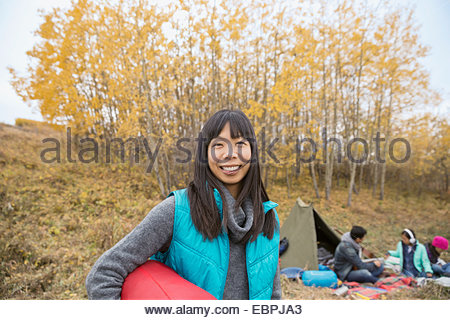 Portrait of smiling woman camping with family - Stock Photo