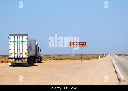 A truck stopped by the Eyre Highway sign informs of the eastern end of treeless plain, the Nullarbor Plain, South - Stock Photo