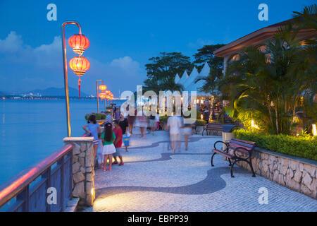 People walking along promenade at dusk, Discovery Bay, Lantau, Hong Kong, China, Asia - Stock Photo