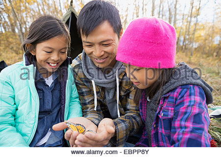 Father showing butterfly to daughters - Stock Photo