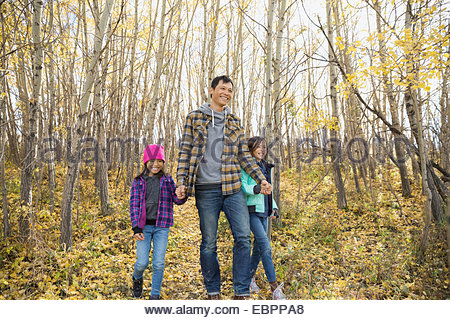 Father and daughters walking in autumn woods - Stock Photo