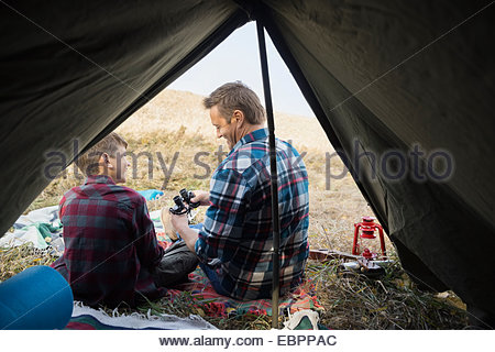 Father and son with binoculars outside tent - Stock Photo