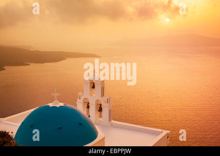 Blue dome and bell tower at sunset, St. Gerasimos church and Aegean Sea, Firostefani, Fira, Santorini, Cyclades - Stock Photo